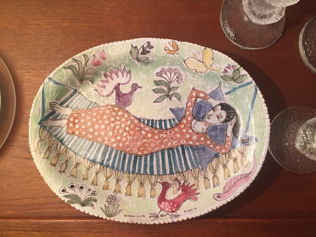 Keramiikkalaatta, Hilkka-Liisa Ahola, Arabia. Lautasen maalauksessa oranssimekkoinen nainen makoilee riippukeinussa puutarhassa, ympärillä on kukkia, perhosia ja lintuja.