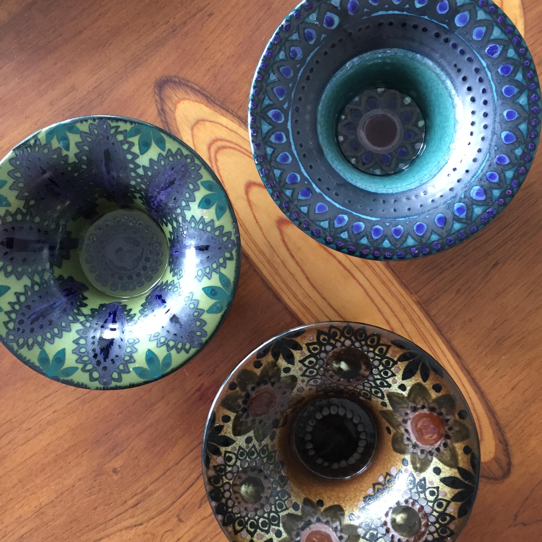 kolme koristeellista keramiikkavatia tai kynttiläkippoa, joissa vihreän, sinisen ja ruskean sävyjä